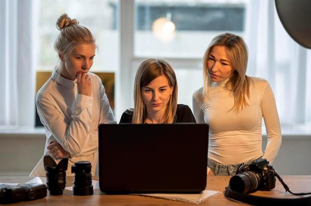 Fotógrafo y modelos mirando fotos vista frontal