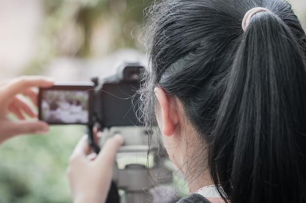 Fotógrafo de la muchacha asiática del estudiante que aprende la atención toma la foto para la afición, cámara en el trípode
