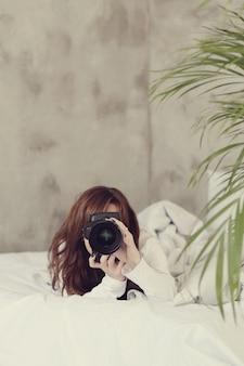 Fotógrafo mujer acostada en la cama con cámara de fotos