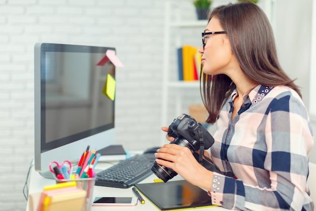 Fotógrafo de la mujer bastante joven con la cámara en oficina