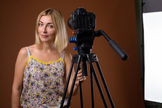 Fotógrafo de mujer con cámara dslr en trípode en studio