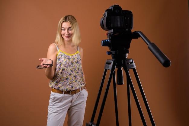 Fotógrafo de mujer con cámara dslr en trípode en studio Foto Premium