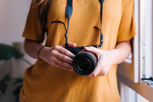 Fotógrafo mujer en casa sosteniendo una cámara