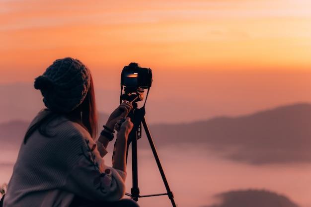 Fotógrafo de la mujer joven que toma la imagen del paisaje cuando salida del sol en el pico de montaña.