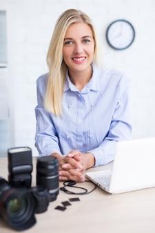 Fotógrafo de mujer sentada con equipo informático y de fotografía en casa o en la oficina