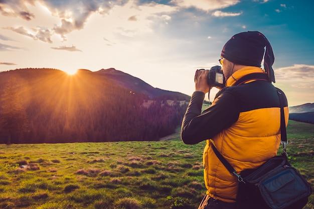 Fotógrafo de naturaleza turística en montañas