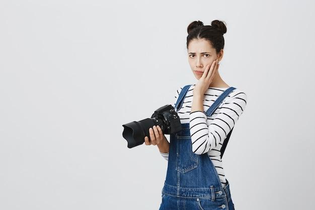 Fotógrafo de niña preocupada que se siente nerviosa. mujer sosteniendo la cámara y se siente molesto