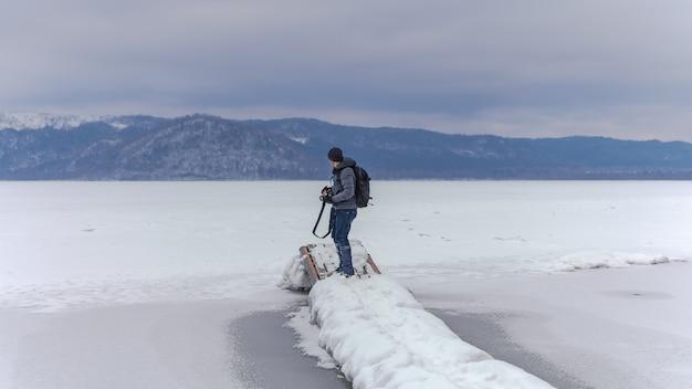 Fotógrafo con paisaje de montaña de nieve