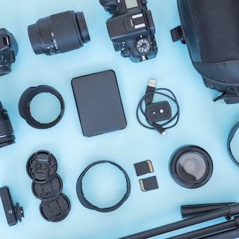 Fotógrafo profesional de accesorios y equipos dispuestos sobre fondo azul.