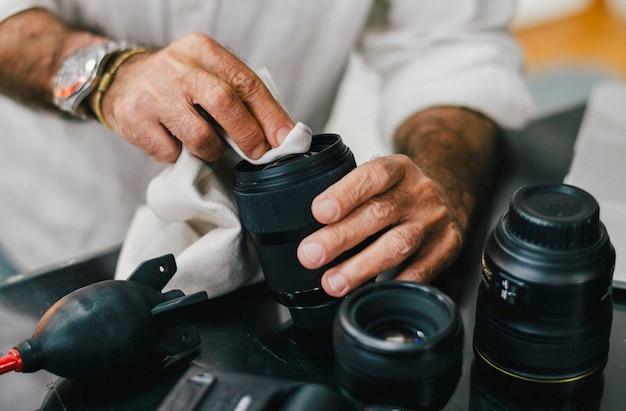 Fotógrafo senior limpiando su lente