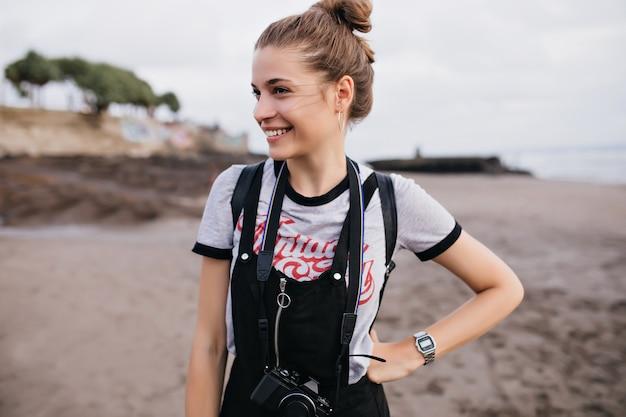 Fotógrafo de sexo femenino agraciado de pie en pose de confianza en la playa. chica agradable en reloj de pulsera de moda sonriendo a la naturaleza.