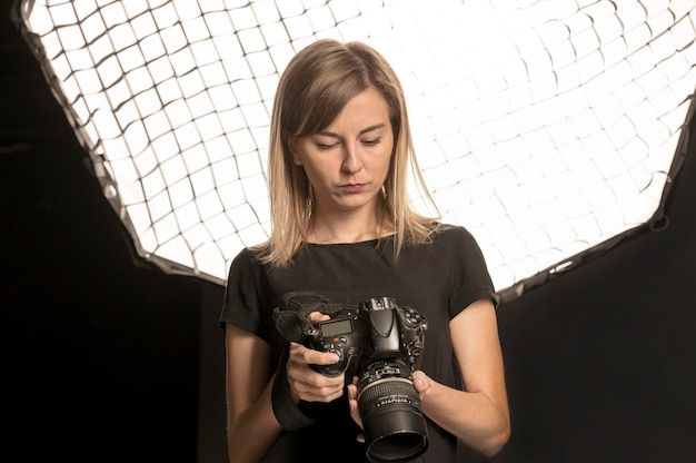 Fotógrafo de sexo femenino que ajusta su cámara