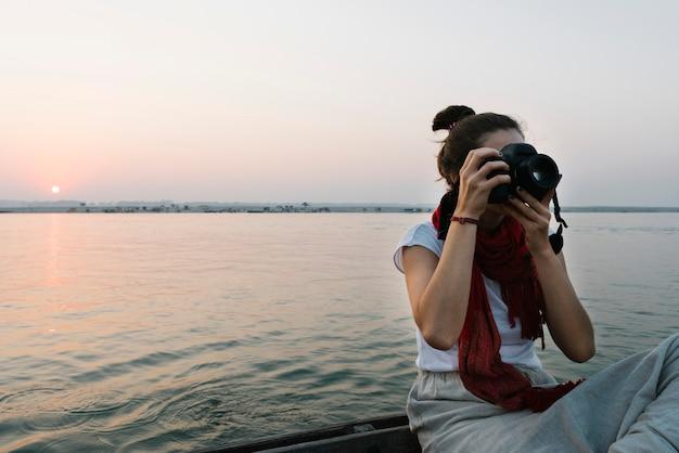 Fotógrafo de sexo femenino que se sienta en un barco en el río ganges