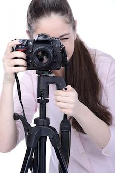Fotógrafo de sexo femenino que sostiene una cámara profesional.