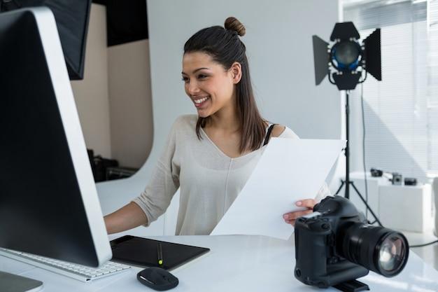 Fotógrafo de sexo femenino que trabaja sobre la computadora en el escritorio