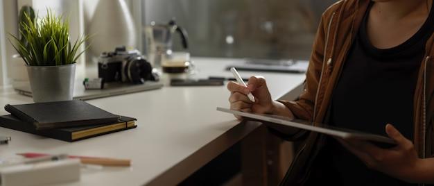 Fotógrafo de sexo femenino que usa la tableta digital mientras está sentado en la mesa de trabajo con suministros, cámara y decoraciones en el estudio