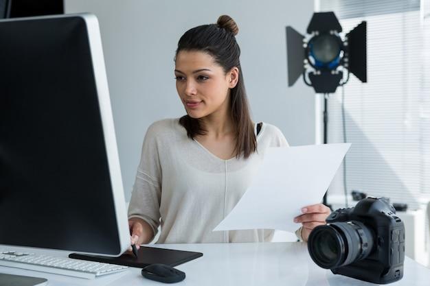 Fotógrafo de sexo femenino que usa la tableta gráfica en el escritorio