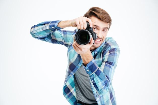 Fotógrafo de sexo masculino feliz que toma la foto en la cámara de fotos aislada en un fondo blanco