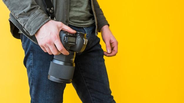 Fotógrafo de sexo masculino que se coloca con la cámara