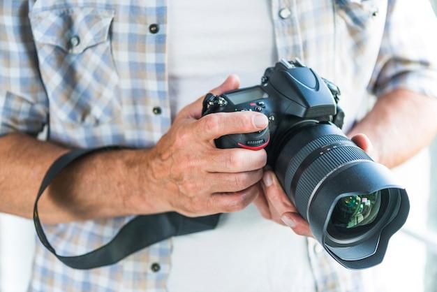 Fotógrafo de sexo masculino que sostiene la cámara de la foto del dslr en manos