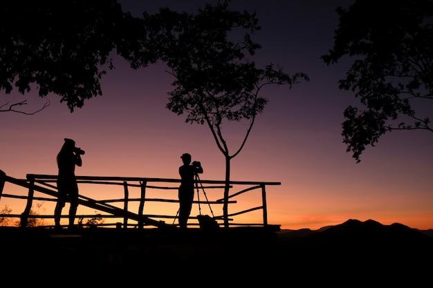 Fotógrafo silueta en la montaña tomando fotos de paisajes con puesta de sol o amanecer - fotógrafo mujer con cámara