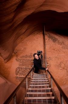 Fotógrafo subiendo escalera en un cañón de ranura, cañón sacacorchos, antelope canyon inferior, antelope canyon, página, arizona, ee.uu.