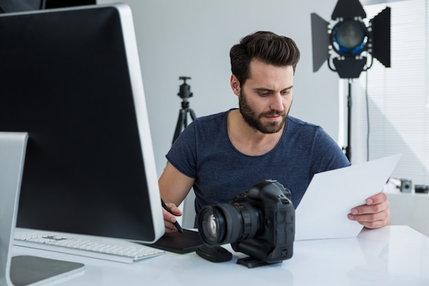Fotógrafo con tableta gráfica en el escritorio