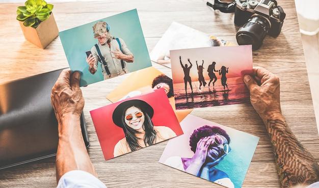 Fotógrafo tatuado en su estudio creativo eligiendo fotos - hombre inconformista en el trabajo editando imágenes tomadas - tendencias laborales, moda y concepto tecnológico - centrarse en las manos