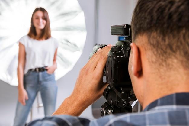 Fotógrafo tomando una foto de una mujer modelo en estudio