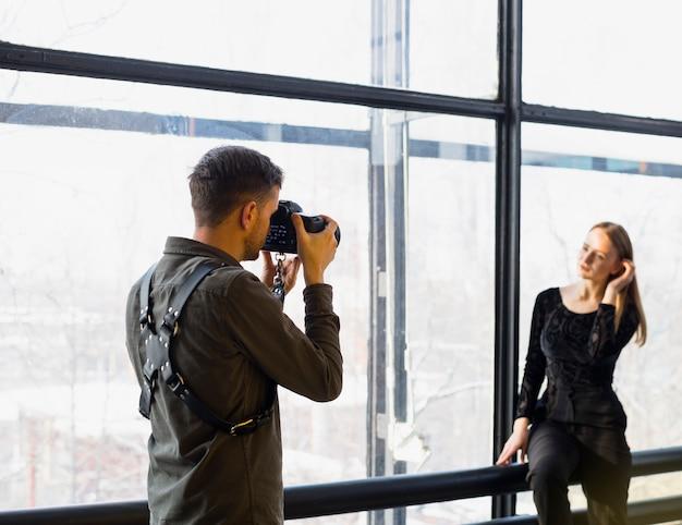 Fotógrafo tomando fotos de joven modelo femenino.