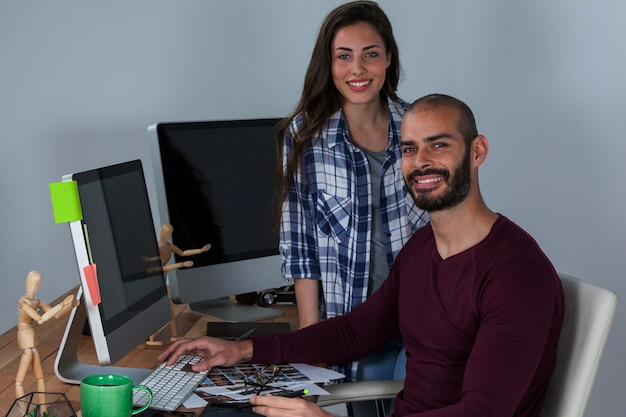 Fotógrafo trabajando en su escritorio con colega