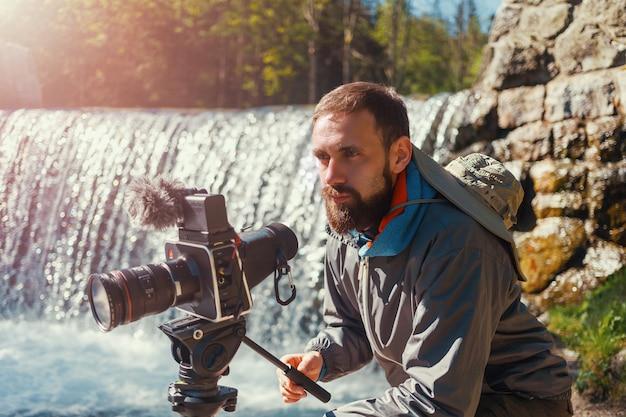 Fotógrafo de viajes hombre barbudo de cerca con cámara de película profesional en trípode disparando paisaje de montaña en el fondo de la cascada