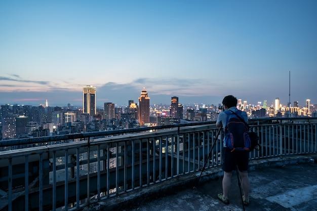 Fotógrafos fotografían paisajes urbanos en el techo de un edificio en chongqing, china