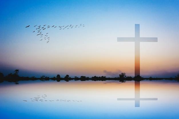 Fotomontaje de cruz contra silhoretote de montaña y vista al lago al atardecer
