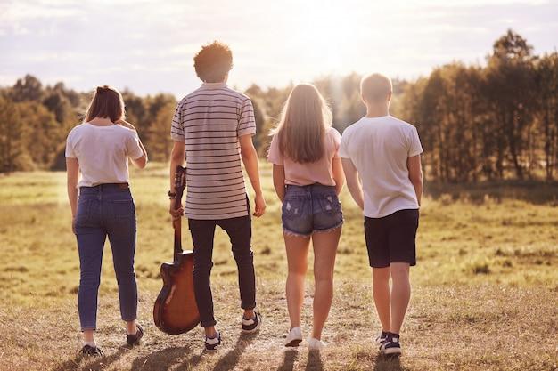 Las fotos al aire libre de los adolescentes dan un paso atrás, caminan por el campo, durante las vacaciones de verano, usan la guitarra para cantar canciones, son fotografiados en movimiento. concepto de juventud, descanso y estilo de vida.