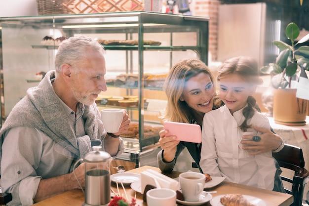 Fotos de familia. abuela de pelo rubio radiante mostrando a su linda chica algunas fotos familiares