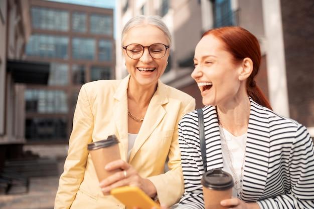Fotos geniales. dos mujeres empresarias riendo de pie al aire libre mientras sostienen tazas de café de papel y miran fotos en el teléfono inteligente