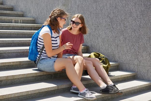 Las fotos de hermosas adolescentes se sientan en las escaleras al aire libre, usan gafas de sol y ropa casual, llevan mochilas, descansan después de clases, discuten las últimas noticias, tienen expresiones alegres. estilo de vida