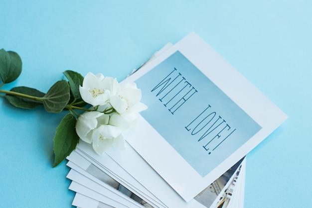 Fotos impresas, tarjetas con marco, sobre fondo azul con flor blanca.