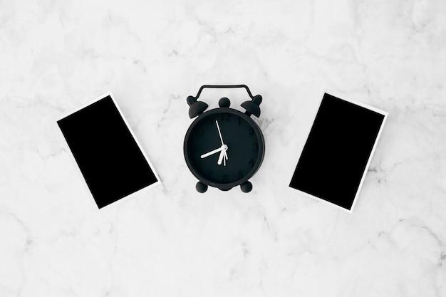 Fotos instantáneas y reloj despertador sobre fondo texturado mármol blanco