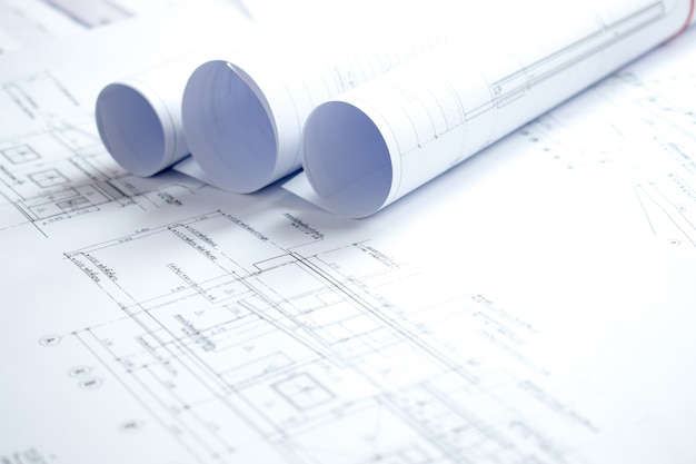 Fotos de primer plano de muchos planes de casa sobre una mesa blanca.