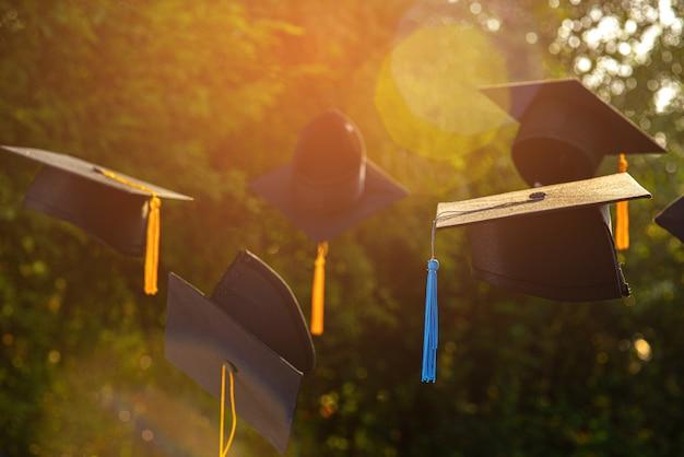 Las fotos de los sombreros de los graduados en el fondo son borrosas.