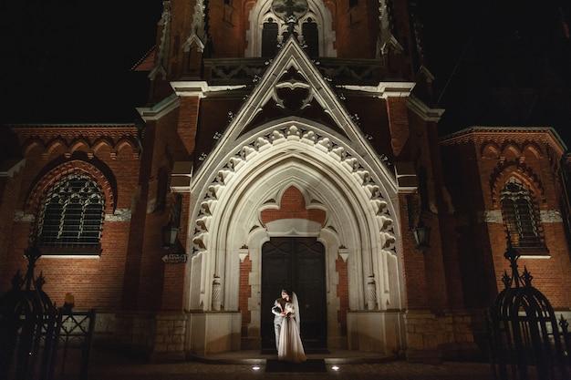 Fotosesión nocturna de novios en cracovia, recién casados pasean por la iglesia