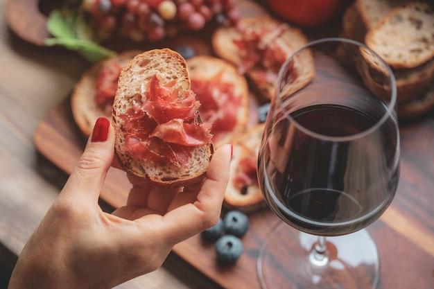 Fouc selectivo en el dedo que sostiene jamón serrano jamón y copas de vino tinto sobre tabla de madera