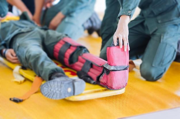 Fractura del paciente de la pierna a astillas en camilla portátil