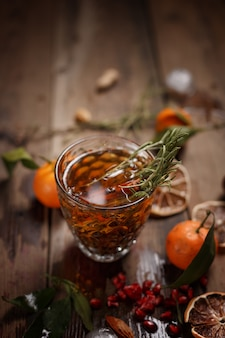 Fragante té de frutas con mandarinas, limones secos y romero en una mesa de madera. estilo rústico.