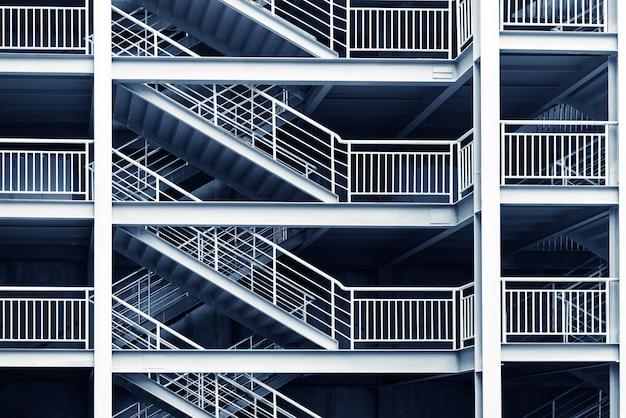 Fragmento abstracto interior moderno con barandas de acero y escaleras de vidrio.