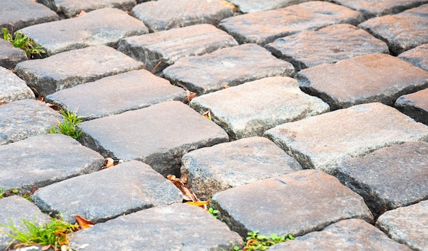 Un fragmento de un antiguo pavimento de adoquines revestido con ladrillos rectangulares multicolores. de cerca. antecedentes. patrón.