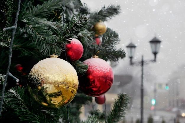 Fragmento de árbol de navidad decorado con bolas rojas y amarillas ligeramente cubierto de nieve al aire libre sobre fondo borroso de linterna y edificios.