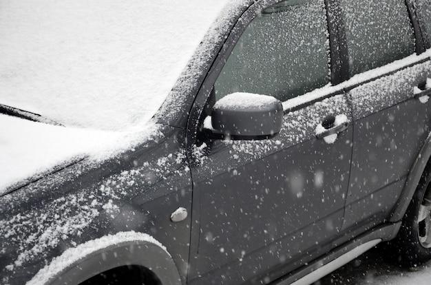 Fragmento del automóvil bajo una capa de nieve después de una fuerte nevada. el cuerpo del coche está cubierto de nieve blanca.